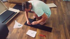 Молодой человек независимо собирает мебель в живущей комнате его дома Человек собирает стол компьютера стоковое фото rf