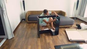 Молодой человек независимо собирает мебель в живущей комнате его дома Человек собирает стол компьютера стоковые изображения