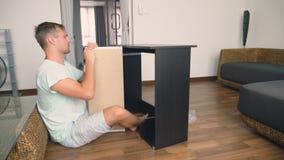 Молодой человек независимо собирает мебель в живущей комнате его дома Человек собирает стол компьютера стоковое фото