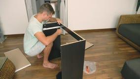 Молодой человек независимо собирает мебель в живущей комнате его дома Человек собирает стол компьютера стоковые фотографии rf