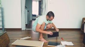 Молодой человек независимо собирает мебель в живущей комнате его дома Человек собирает стол компьютера стоковое изображение rf