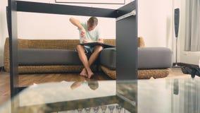 Молодой человек независимо собирает мебель в живущей комнате его дома Человек собирает стол компьютера стоковые фото