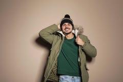 Молодой человек нося теплые одежды на предпосылке цвета готовая каникула стоковая фотография rf