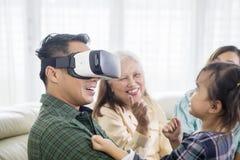 Молодой человек нося шлемофон VR с его семьей стоковое изображение rf