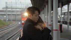 Молодой человек обнимает женщину стоя на железнодорожном вокзале outdoors Многонациональный сток-видео