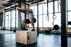 Молодой человек одетый в черных одеждах спорт делает сидения на корточках на коробке рядом с оборудованием спорта в спортзале стоковое фото