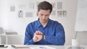 Молодой человек ослабляя на кресле и используя применения Smartwatch видеоматериал