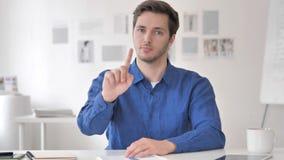 Молодой человек отвергая предложение пока сидящ на рабочем месте сток-видео