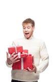 Молодой человек падает много красных подарков рождества Стоковые Фотографии RF