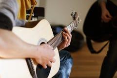 Молодой человек певец-соло на акустической гитаре стоковое изображение rf
