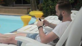Молодой человек печатает messege на его smartphone около бассейна акции видеоматериалы