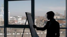 Молодой человек пишет на whiteboard стоя на предпосылке окна в современном интерьере акции видеоматериалы