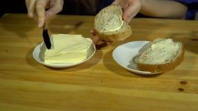 Молодой человек подготавливая сандвич, распространения умаслит на хлебе акции видеоматериалы