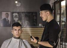 Молодой человек подготовлен получить стрижку счастливым парикмахером пока сидящ в стуле на парикмахерскае Стоковые Фото