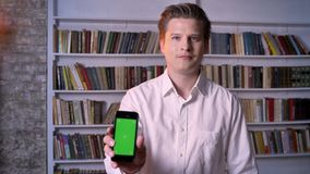 Молодой человек показывает зеленый экран smartphone в библиотеке, наблюдая на камере, концепция связи сток-видео