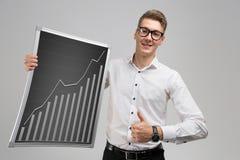 Молодой человек показывает знак класса и держит поднимая диаграмму изолированный на белой предпосылке стоковое изображение