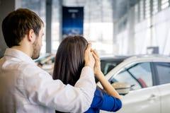 Молодой человек покрывает глаза его подруги стоя перед автомобилем Стоковые Изображения RF