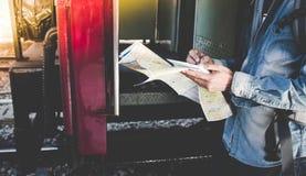 Молодой человек получает в международный поезд один с картой перемещения на платформе в железнодорожном вокзале Стоковое фото RF