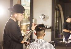 Молодой человек получая стрижку парикмахером пока сидящ в стуле на парикмахерскае Стоковые Изображения RF