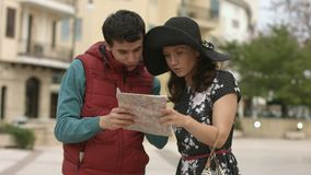 Молодой человек помогая милой женщине найти путь к гостинице, показывая направление на карте видеоматериал