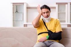 Молодой человек после аварии страдая дома стоковое изображение