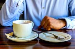 Молодой человек после приятного чаепития отдыхая и говоря по телефону в кафе бизнес-ланч, деловые встречи стоковые изображения