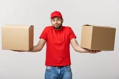 Молодой человек поставки в красной форме держа 2 пустых картонной коробки изолированный на белой предпосылке Скопируйте космос дл Стоковые Фотографии RF