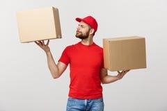 Молодой человек поставки в красной форме держа 2 пустых картонной коробки изолированный на белой предпосылке Скопируйте космос дл Стоковая Фотография