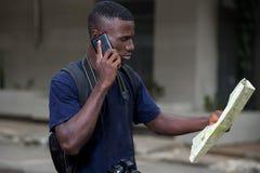 Молодой человек по телефону с картой стоковые изображения