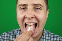 Молодой человек принимая таблетку стоковое изображение rf