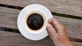 Молодой человек принимая чашку горячего кофе Americano от деревянного стола в взгляде кафа сверху конец замедленного движения 4K  видеоматериал