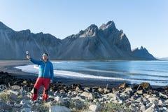 Молодой человек принимая selfie на исландском пляже стоковое изображение rf