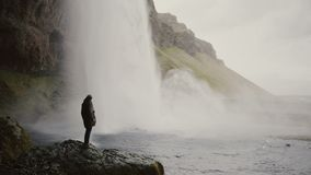 Молодой человек при камера действия стоя близко к водопаду Gljufrabui в Исландии и снимая видео потока воды видеоматериал