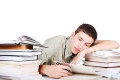 Молодой человек при много книг распологая и писать стоковые изображения