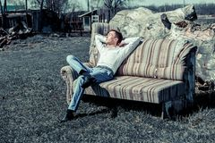 Молодой человек при мои закрытые глаза в голубых брюках сидит стоковые изображения rf