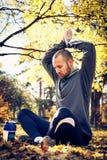 Молодой человек при оружия вверх делая тренировку йоги напольно Стоковая Фотография RF