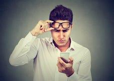Молодой человек при стекла имея тревогу видя сотовый телефон имеет проблемы зрения Плохое текстовое сообщение стоковая фотография rf