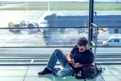 Молодой человек проверяя его телефон пока ждущ его полет в воздух стоковое фото