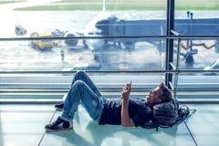 Молодой человек проверяя его телефон пока ждущ его полет в воздух стоковые фотографии rf