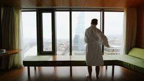 Молодой человек просыпая вверх на роскошной гостинице квартир Успешный купальный халат мужск человека нося и протягивать делающ у акции видеоматериалы