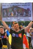 Молодой человек протестуя с другими тысячами людей стоковая фотография
