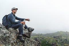 Молодой человек путешественника сидя на верхней части и держа Thermos в его руке Пешая концепция туризма приключения стоковые изображения rf