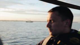 Молодой человек путешествует на шлюпке морским путем в Африке рано утром Красивый ландшафт, парусник на горизонте видеоматериал