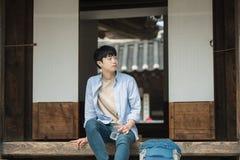 молодой человек путешествуя к Корее принимает остатки с средством воды стоковые фото