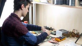Молодой человек работая с вентилятором C.P.U. более крутым на зеленой материнской плате ПК сток-видео
