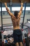 Молодой человек работая с тренажером на спортзале: Задний взгляд Стоковое Изображение