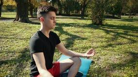 Молодой человек размышляя в половинном лотосе - красивом парке как предпосылка Мальчик одет в черной футболке и красных шортах видеоматериал