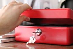 Молодой человек раскрывает денежный ящик безопасности используя ключ стоковое фото