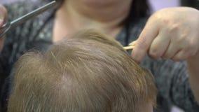 Молодой человек режет волосы в парикмахерской r сток-видео