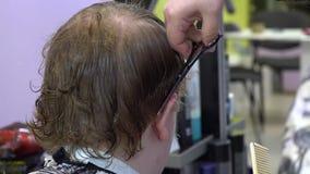 Молодой человек режет волосы в парикмахерской r акции видеоматериалы